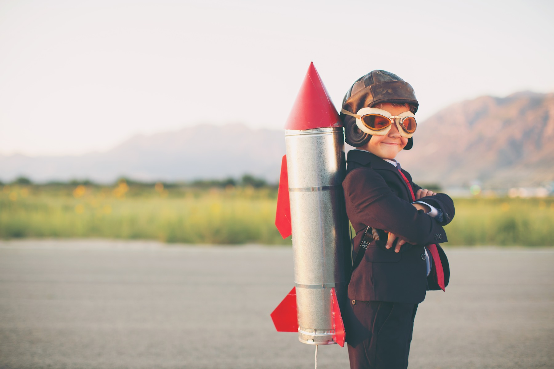 A young business minded boy is wearing a business suit, space helmet with a rocket strapped to his back. His hands are on his hips and he is smiling at the camera standing on blacktop. Plenty of copy space for your innovative type. Image taken in Utah, USA.